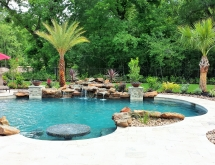 Travertine Pool Accented with a Moss Rock Waterfall, Stone Columns, Fire Bowls and Lush Landscaping