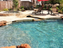 Travertine Spa Flowing into a Flagstone/Pebble Creek with a Bridge Leading to the Fire Pit
