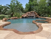 Pool with Large Beach Entry and Weeping Rocks and Slide