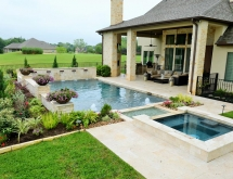 Travertine Pool and Decking. Raised Spa That Flows into a Creek. Travertine Pool and Decking. Raised Spa That Flows into a Creek. Raised Beams Accented with Copper Scuppers. Raised Beams Accented with Copper Scuppers